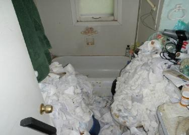 Gross filth - soiled adult diapers piled high in bathroom