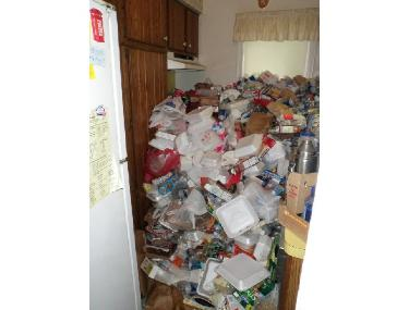 Kitchen of a hoarder's house with trash piled to height of range hood