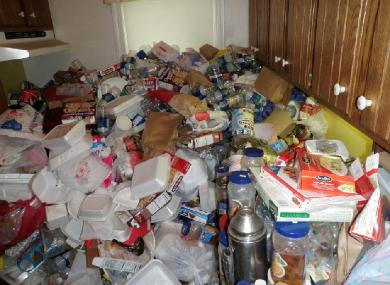 Kitchen of hoarder's house with trash piled 5 feet high