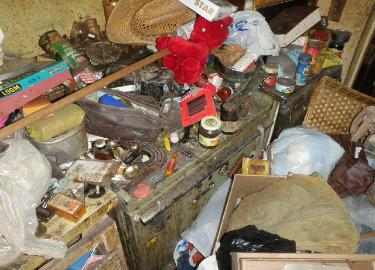 Hoarder kitchen stove piled with trash & filth